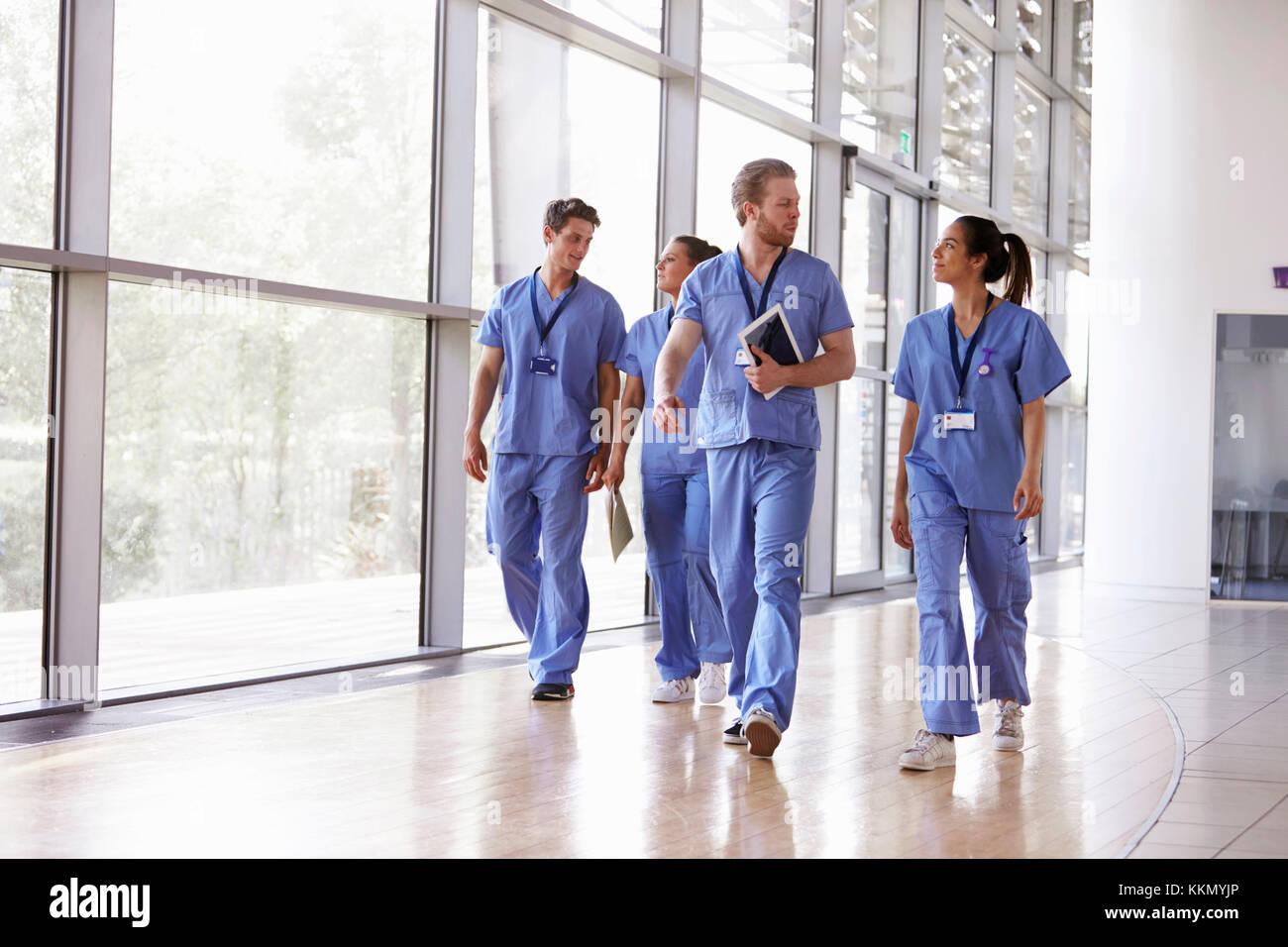 Four healthcare workers in scrubs walking in corridor - Stock Image