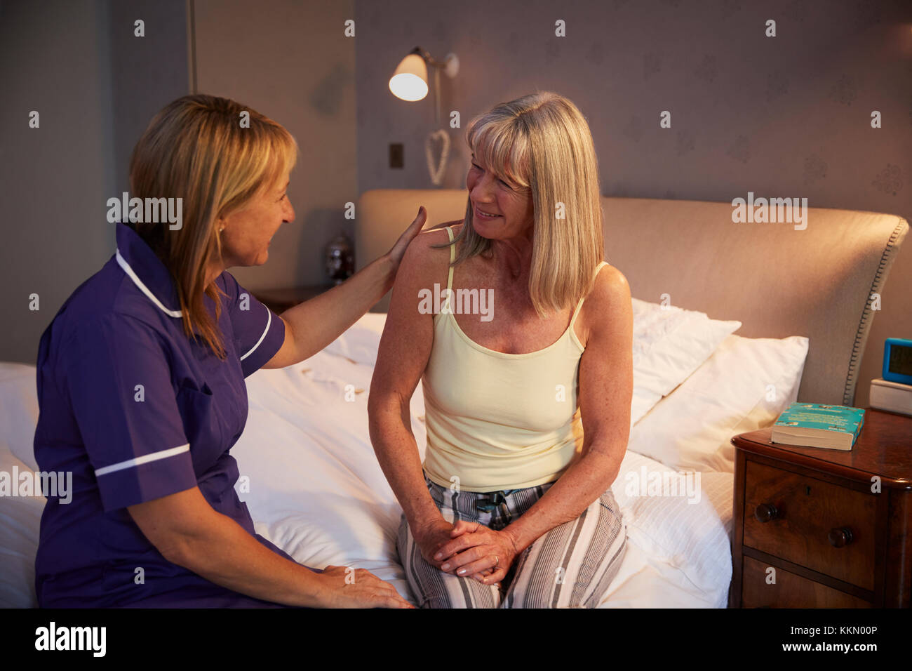 Nurse Talking With Senior Woman In Bedroom On Home Visit Stock Photo