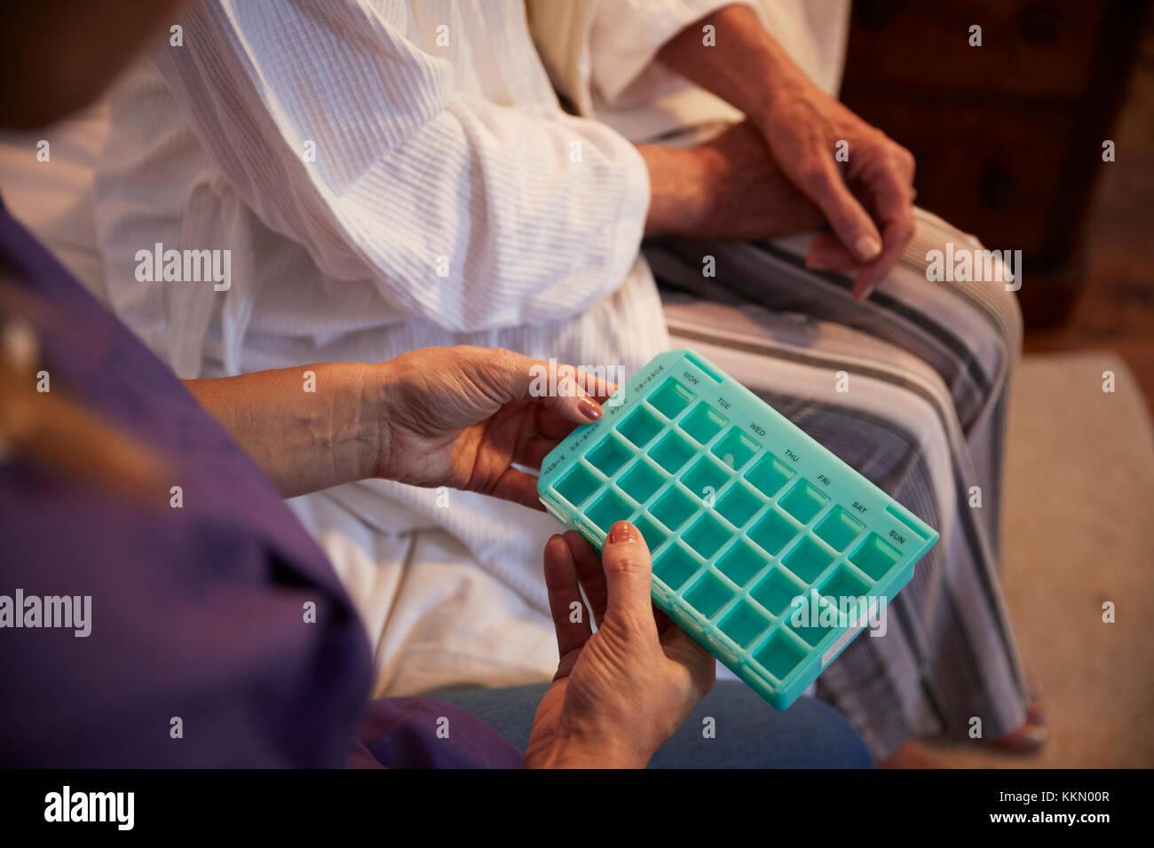 Nurse Helping Senior Woman To Organize Medication On Home Visit - Stock Image