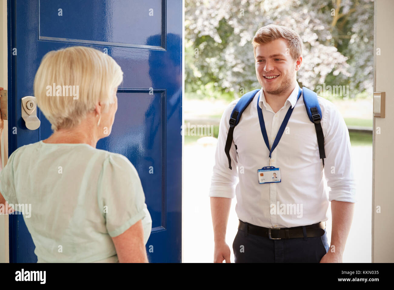 Senior woman greeting male care worker making home visit - Stock Image