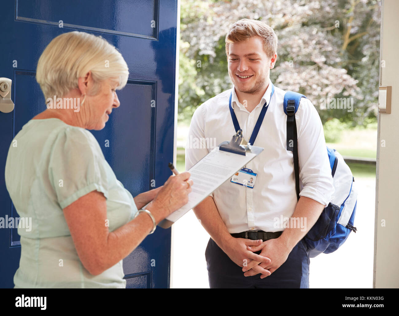 Senior woman filling in survey for visitor at her front door - Stock Image