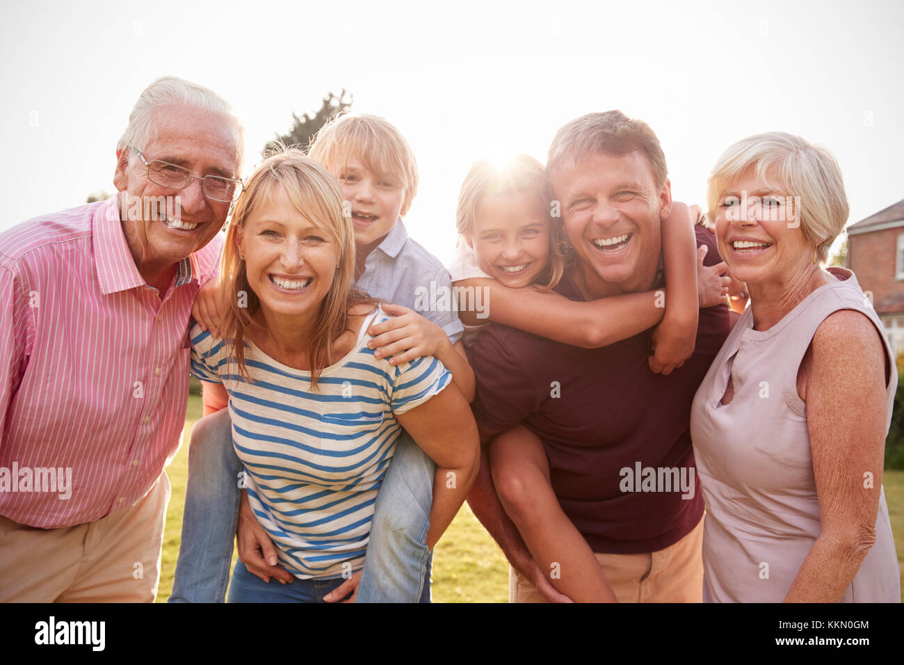 Multi generation family in garden smile to camera, close up - Stock Image