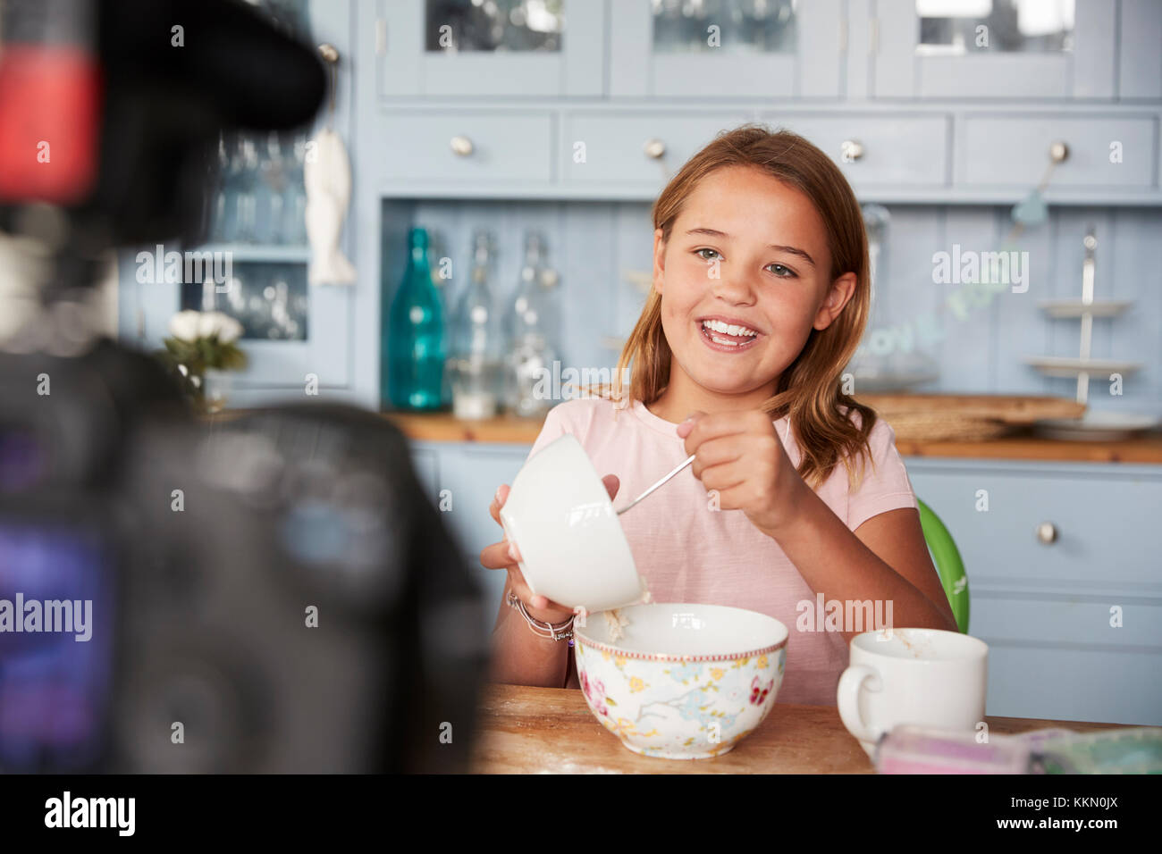 Pre-teen girl video blogging in kitchen mixing ingredients - Stock Image