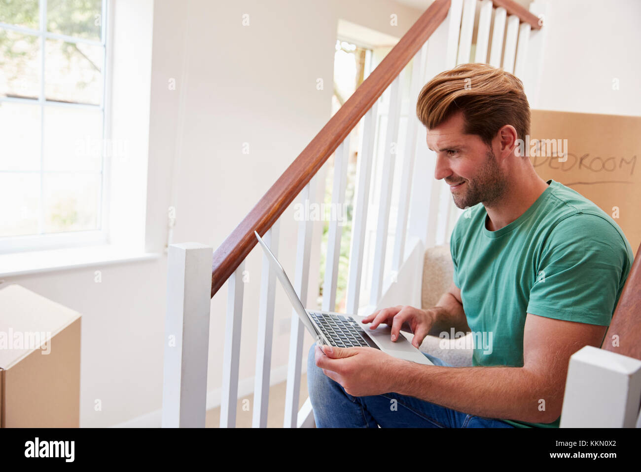 Man Moving Into New Home Looking At Personal Finances On Laptop - Stock Image