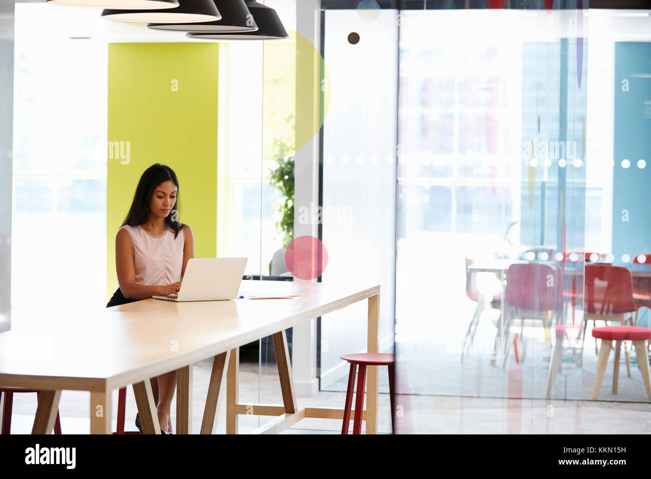 Young black woman working alone in an office meeting area - Stock Image