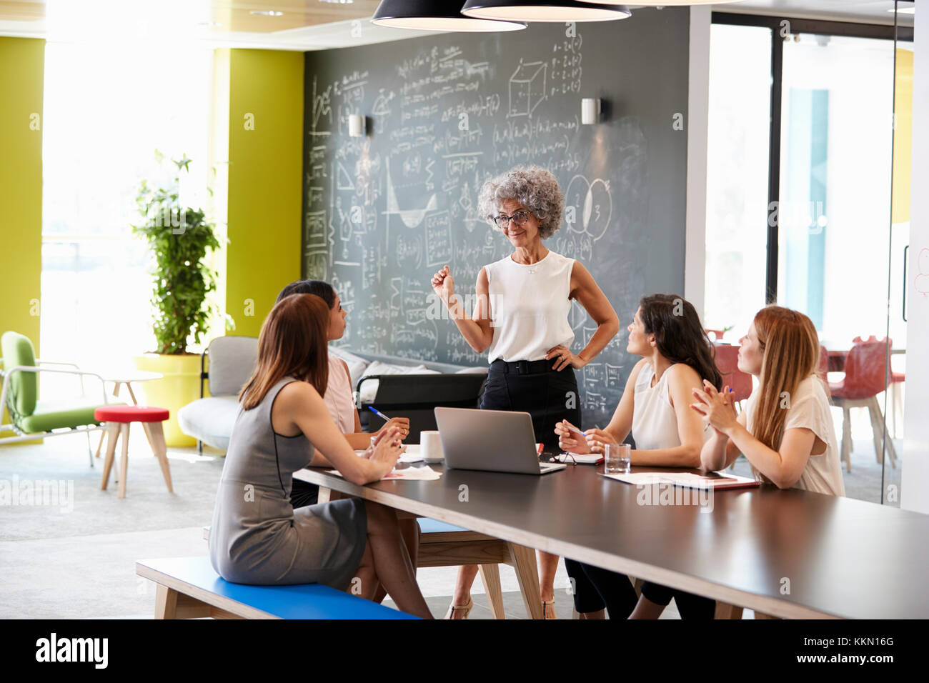 Female boss standing at an informal team meeting - Stock Image