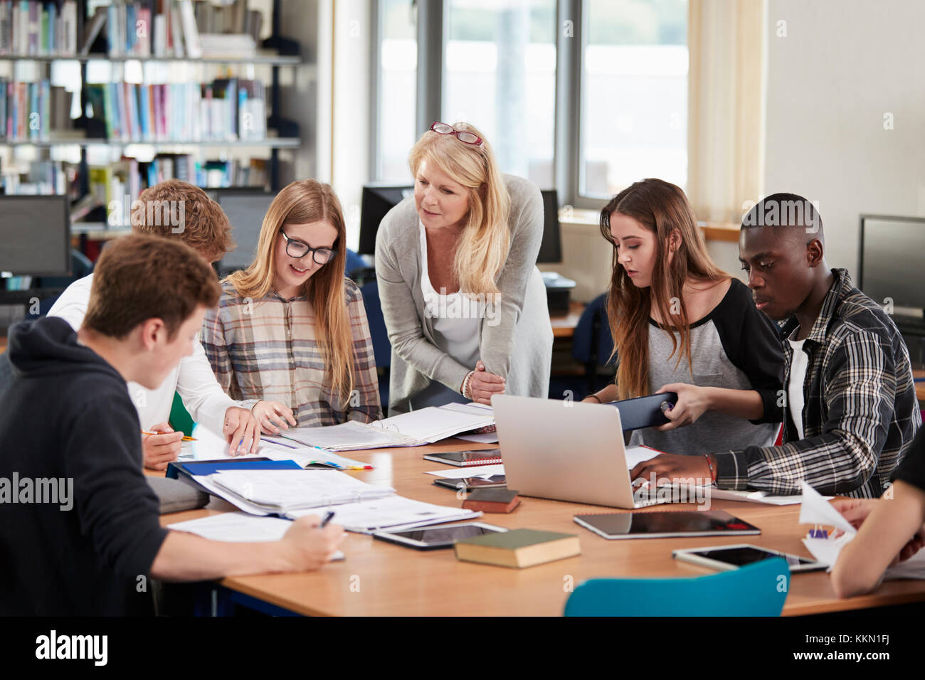 Female Teacher Working With College Students In Library - Stock Image