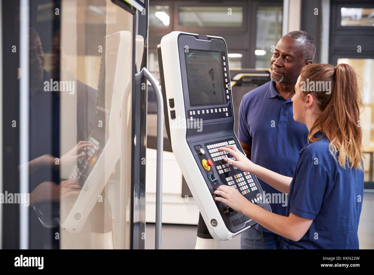 Engineer Showing Apprentice How To Use CNC Tool Making Machine - Stock Image