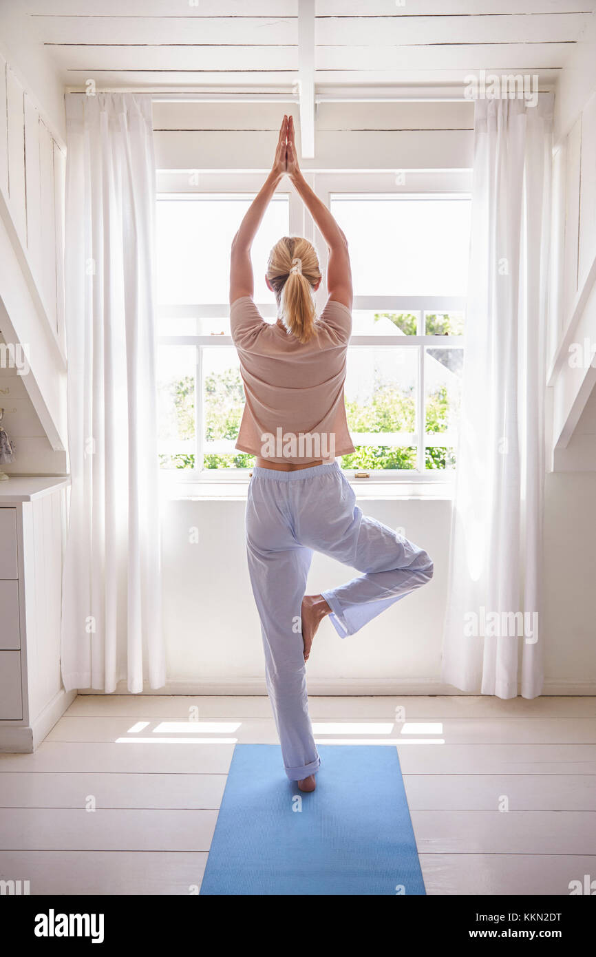 Woman At Home Starting Morning With Yoga Exercises In Bedroom - Stock Image