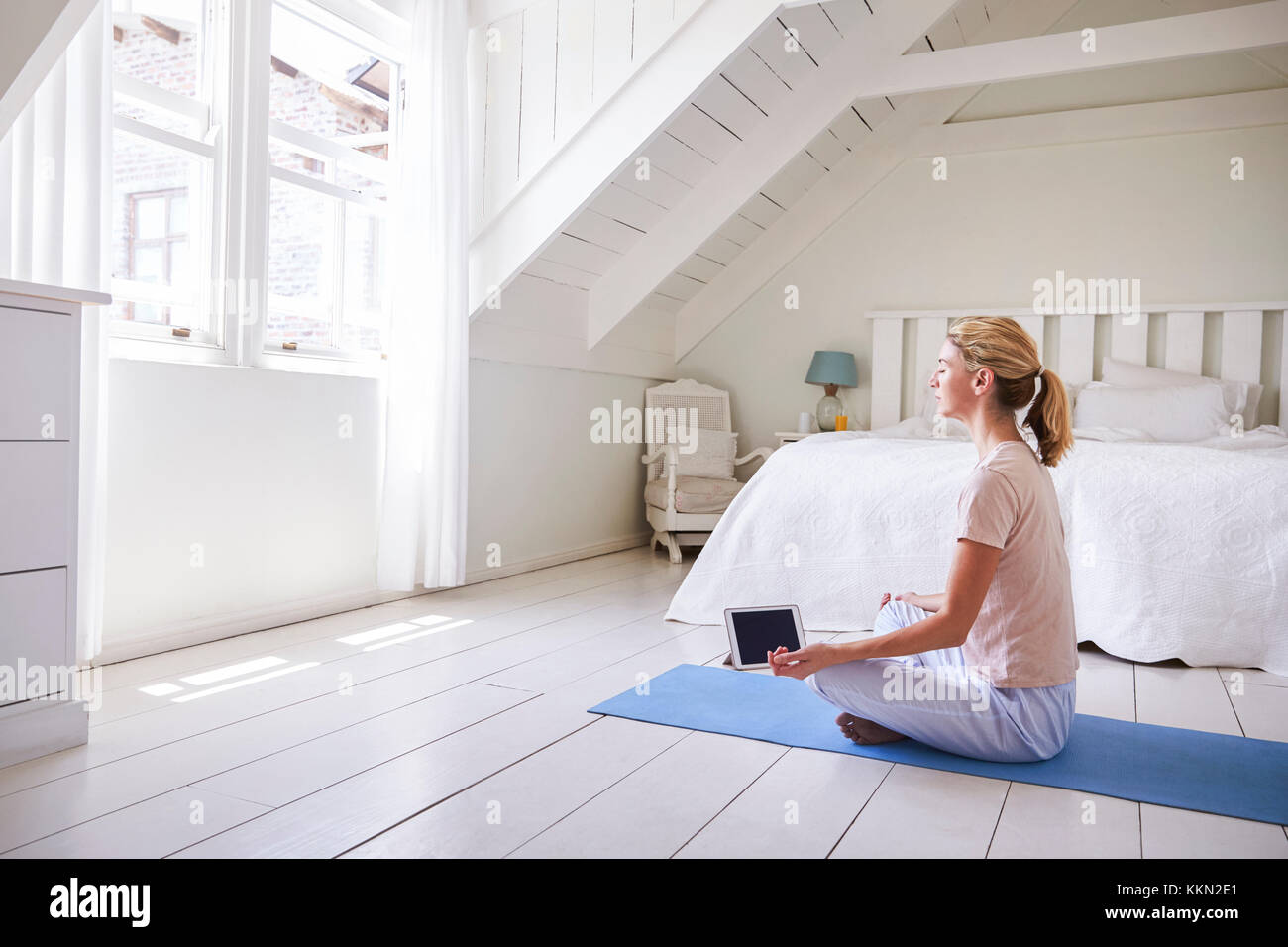 Woman With Digital Tablet Using Meditation App In Bedroom - Stock Image