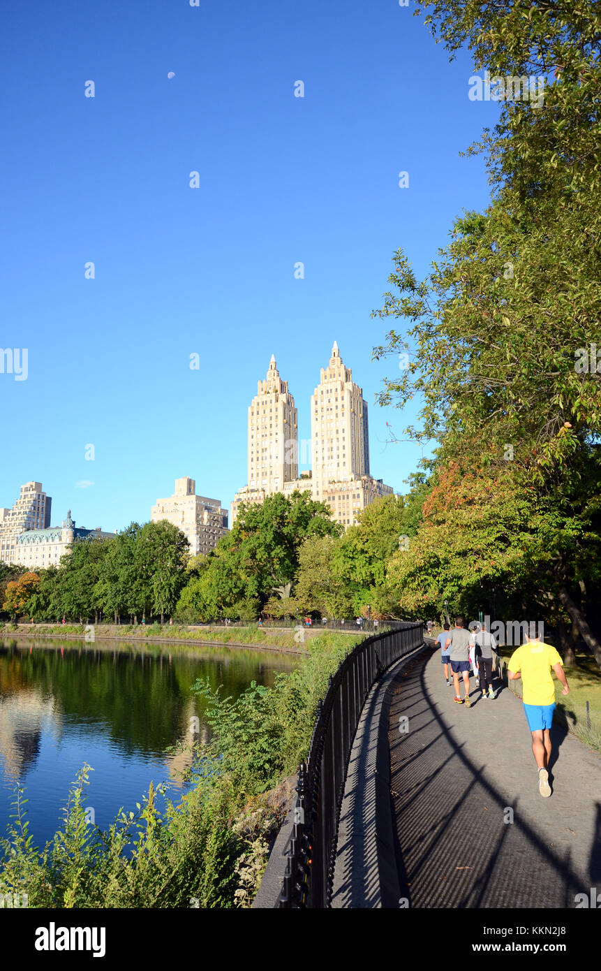 Joggers run around the Schuman Running Track in Central Park with The San Remo building in the background - Stock Image