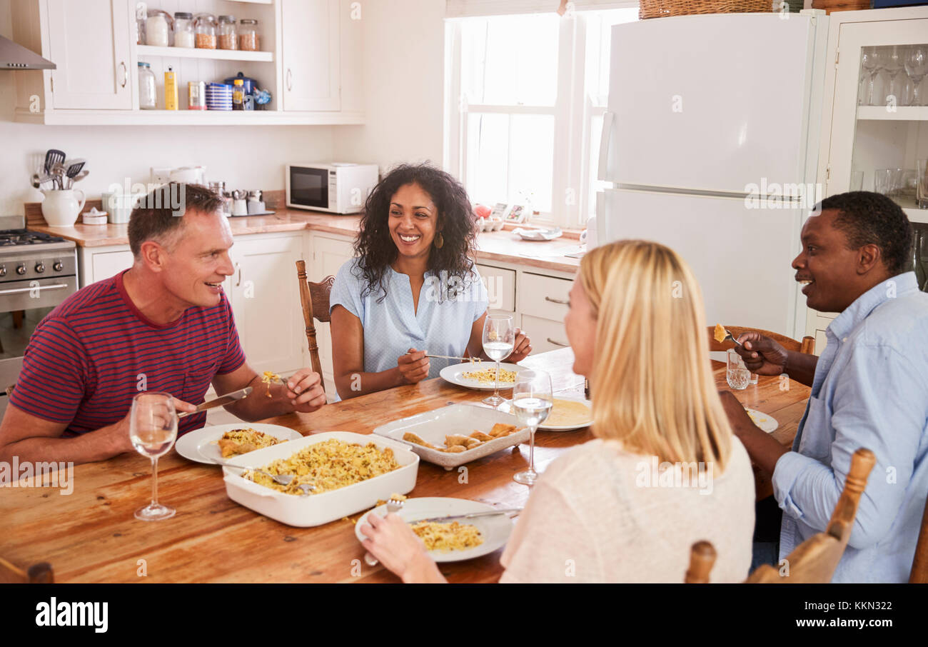 Mature Couple Entertaining Friends At Dinner Party - Stock Image