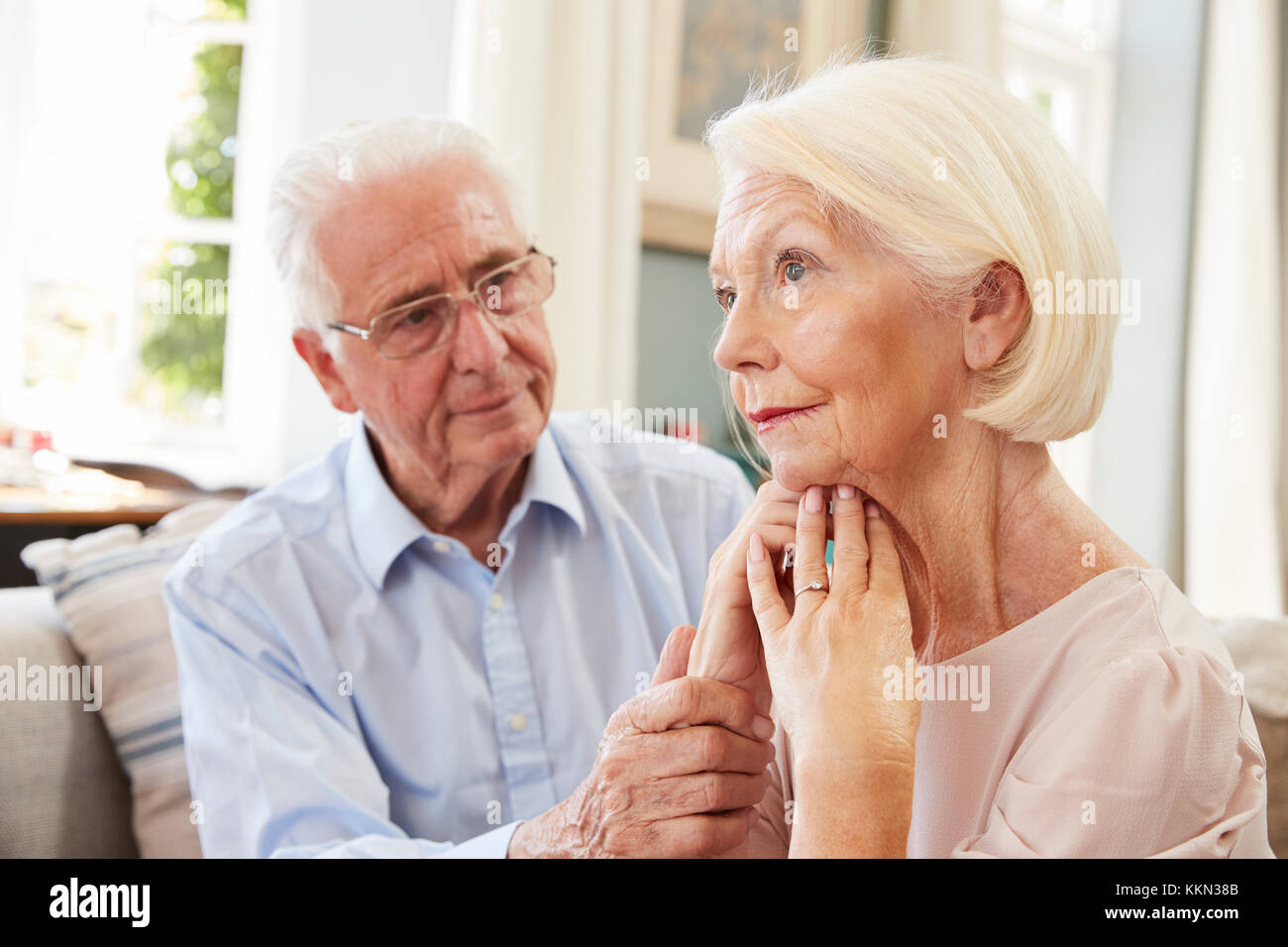 Senior Man Comforting Woman With Depression At Home Stock Photo