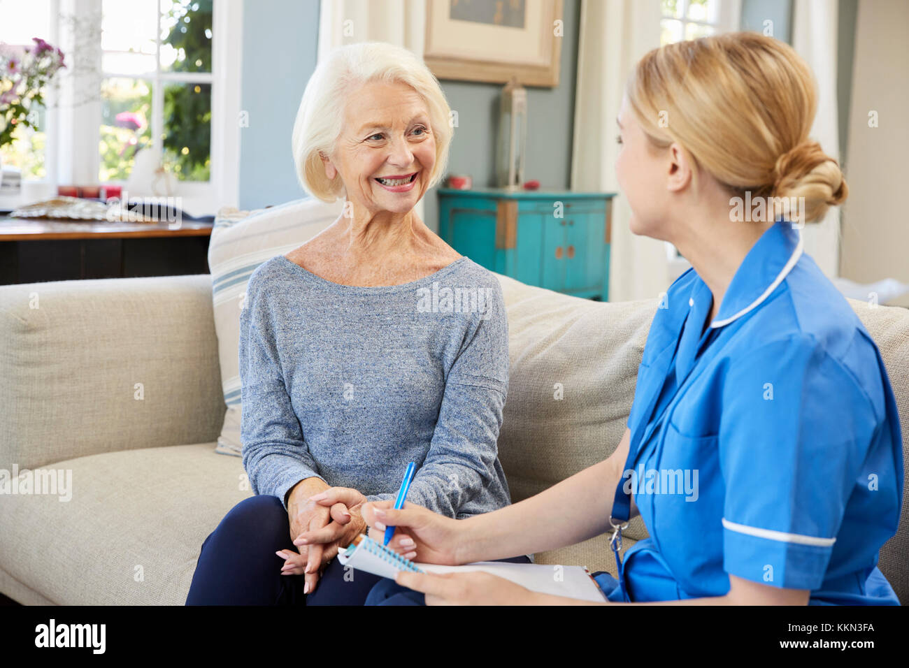 Female Community Nurse Visits Senior Woman At Home - Stock Image