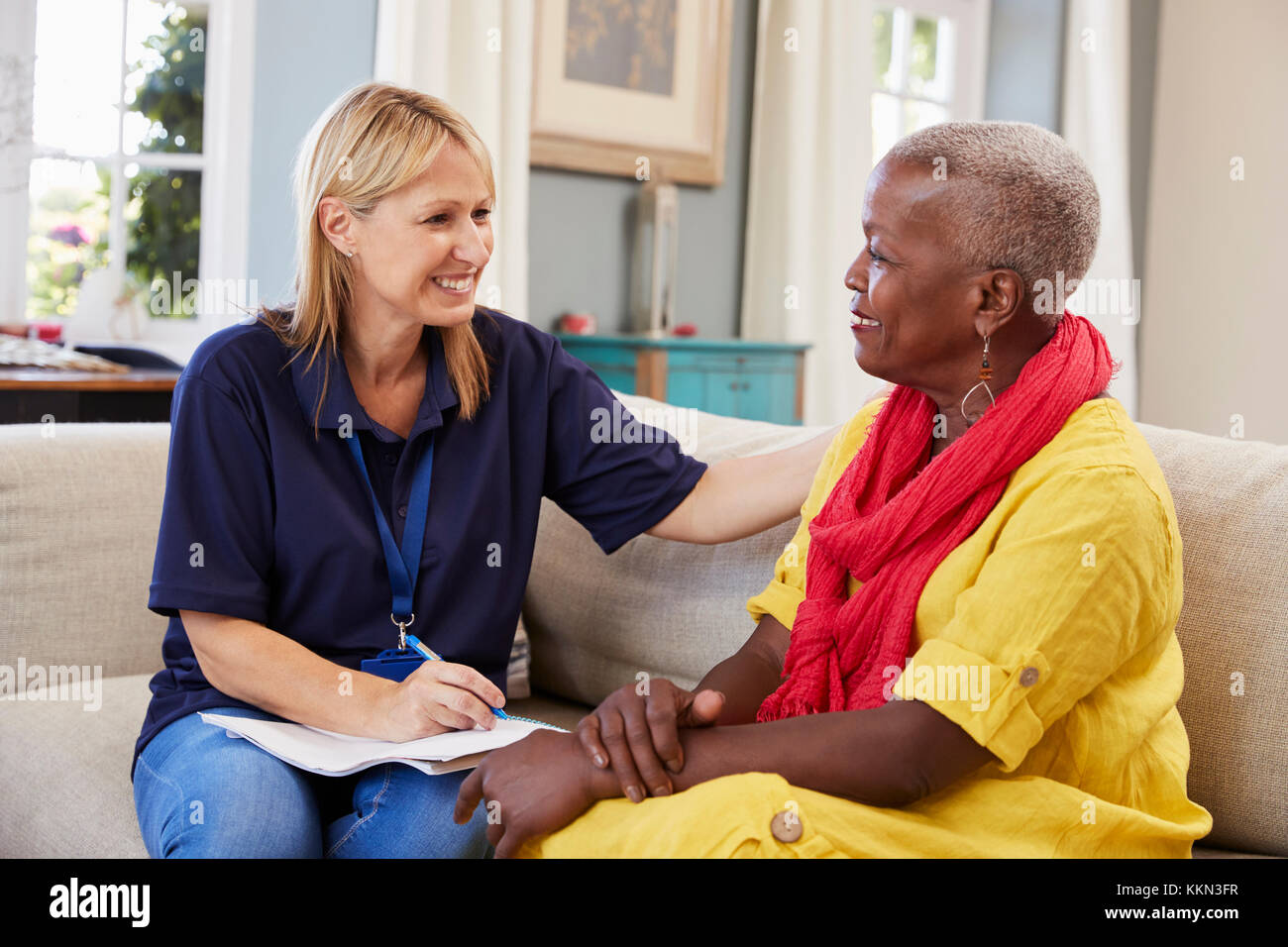 Female Support Worker Visits Senior Woman At Home - Stock Image