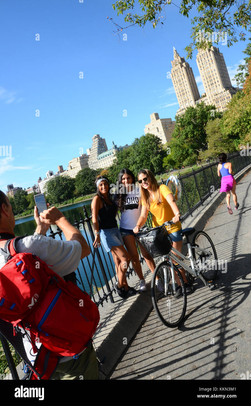 Three female cyclists have their photo taken on the Shuman Running track by the Jacqueline Kennedy-Onassis Reservoir, - Stock Image