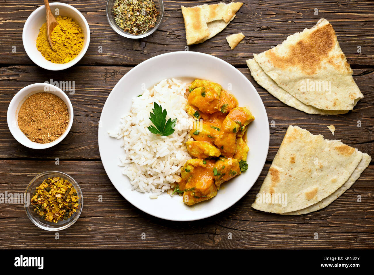 Delicious chicken curry with rice on wooden background. Top view, flat lay - Stock Image