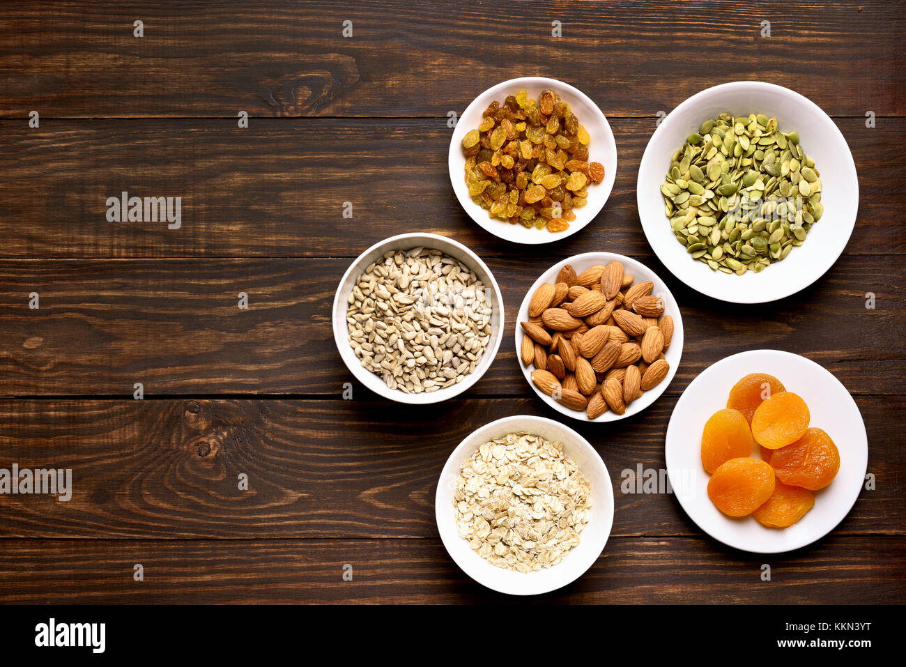 Bowl with ingredients for cooking granola on wooden background with copy space. Top view, flat lay - Stock Image