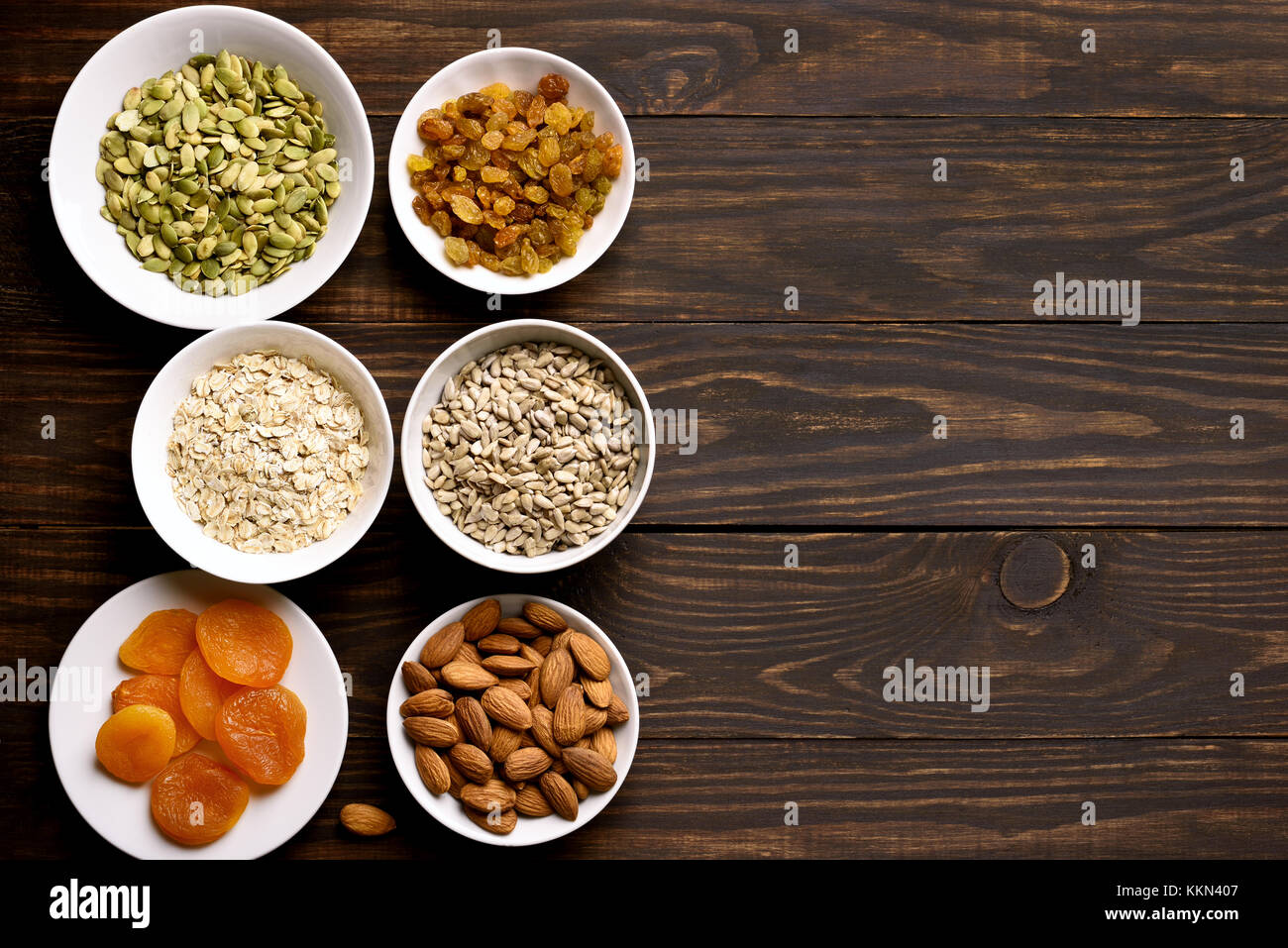 Ingredients for cooking granola on wooden background with copy space. Healthy snack in bowl. Top view, flat lay - Stock Image