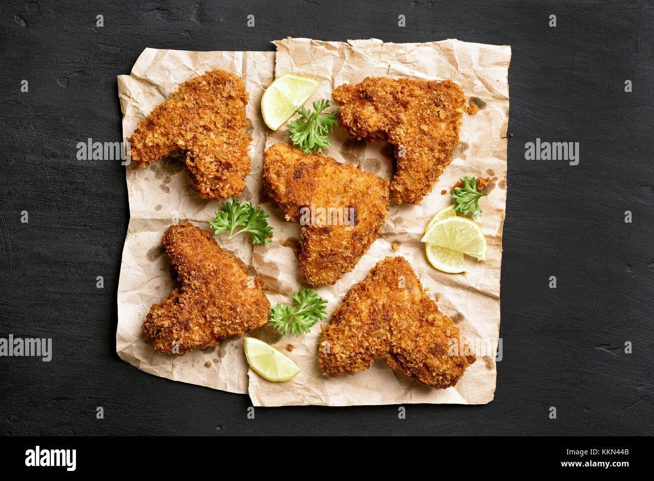 Spicy fried breaded chicken wings on paper over dark black background. Top view, flat lay - Stock Image