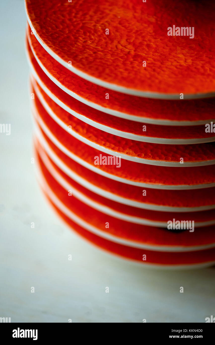 The color of the sun. Warmth. Bright orange dishes in the style of a Mandarin or orange. Ceramics . A stack of saucers - Stock Image