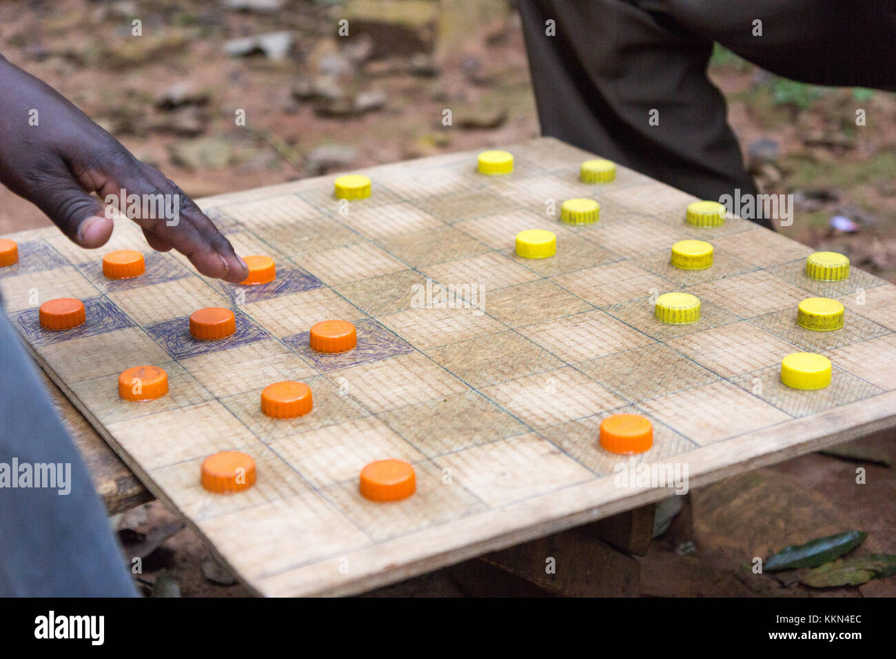 Ugandan men playing draughts (checkers) with plastic bottle lids serving as pieces. - Stock Image