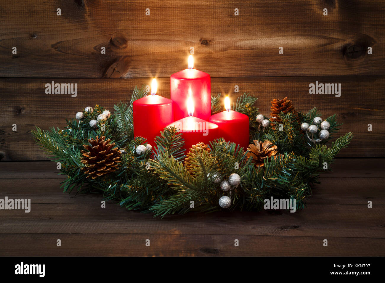 Fourth Advent - Decorated Advent wreath with four red burning candles on a wooden background. - Stock Image