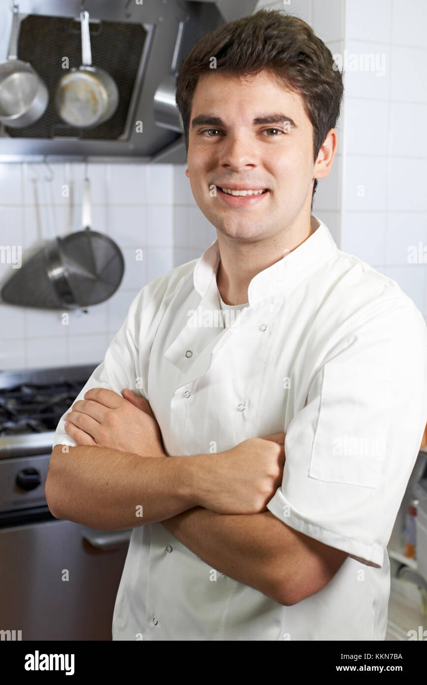 Portrait Of Male Chef Standing In Kitchen - Stock Image