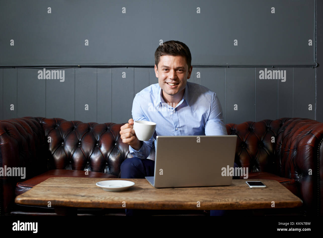 Businessman Drinking Coffee Whilst Working On Laptop In Internet Cafe - Stock Image