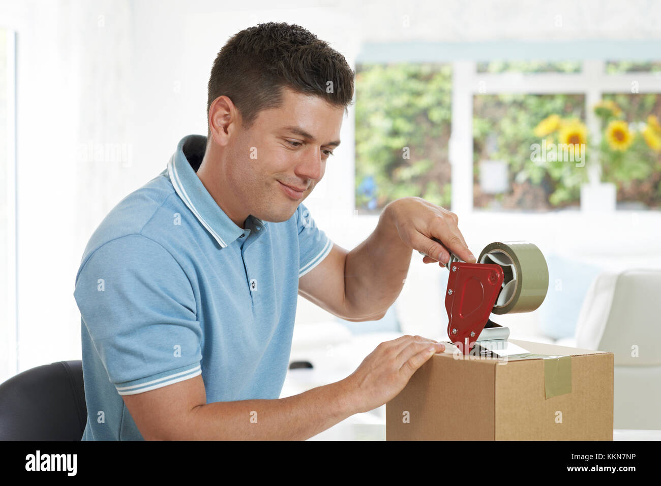 Man At Home Sealing Box For Dispatch - Stock Image
