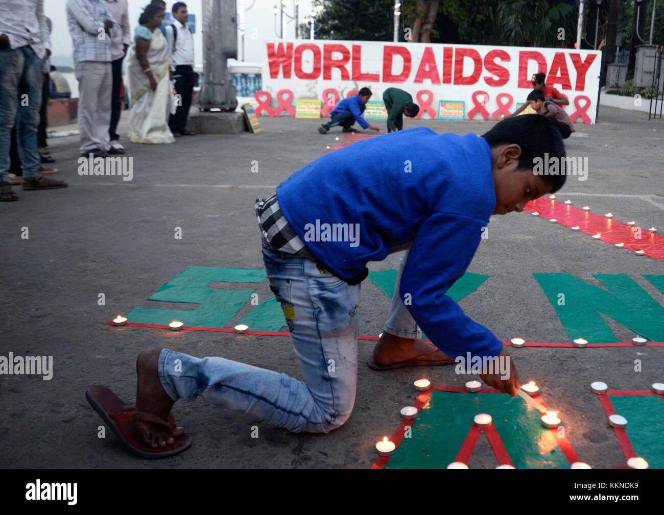Kolkata, India. 01st Dec, 2017. Children lit lamps on Red Ribbon and slogan during a social awareness generation - Stock Image
