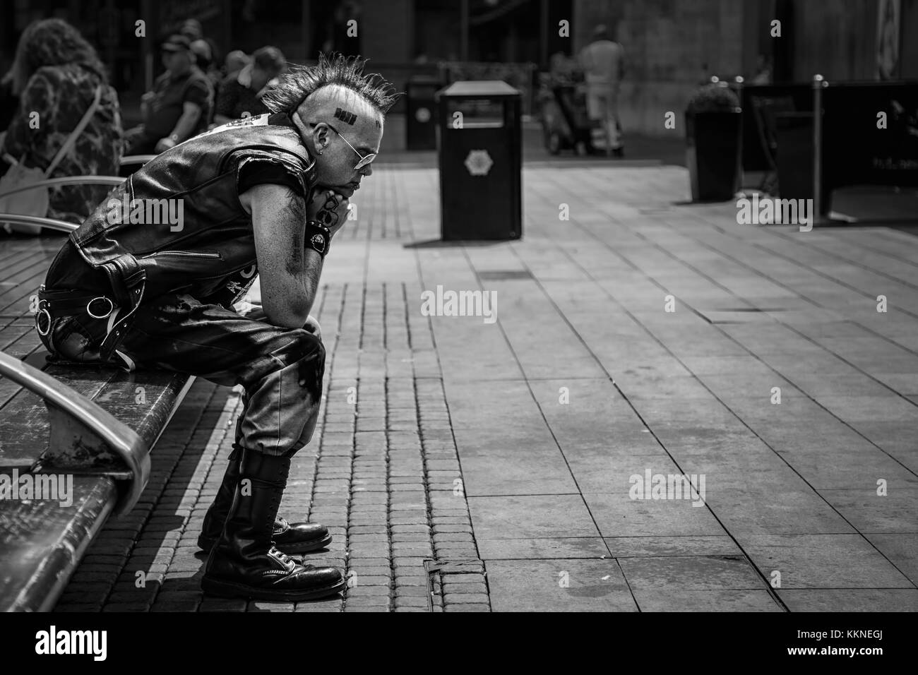 Punk Rocker Sat in Piccadilly Gardens in Manchester City Centre, England, UK - Stock Image