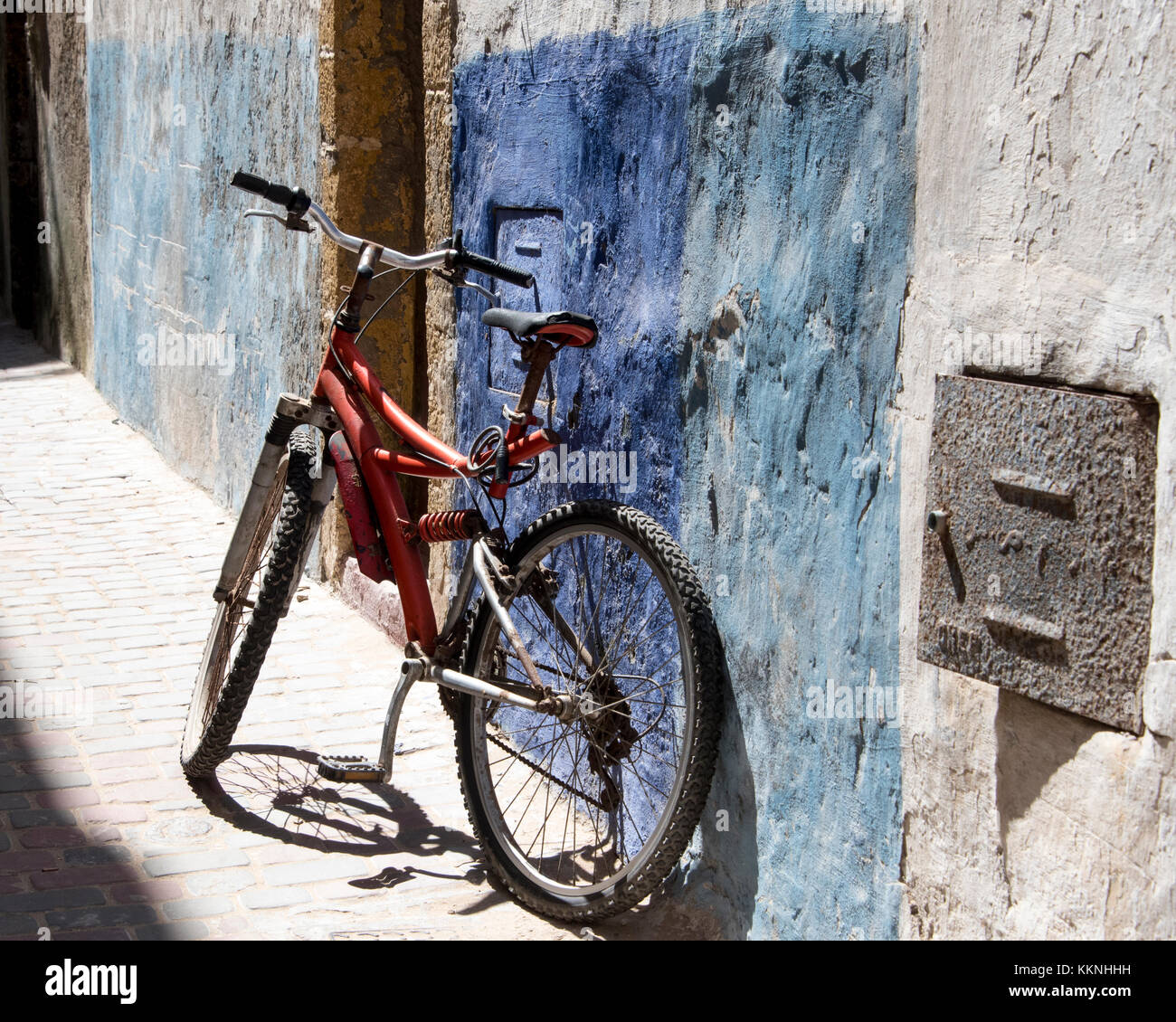 Old bike in a patch of sunlight, leaning against an Alley wall of the Medina Stock Photo