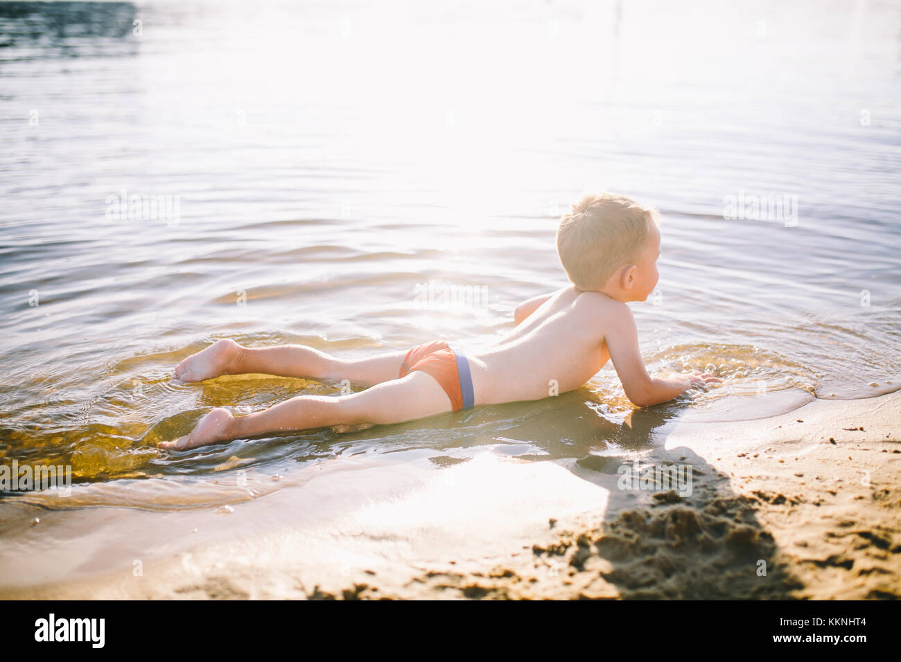 A Caucasian child of three years in red swimming trunks lies on his stomach in the water near the river bank of - Stock Image