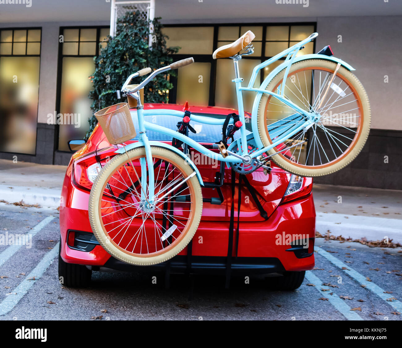 Blue bicycle with basket fastened to back of red sports car parked in front of shops Stock Photo