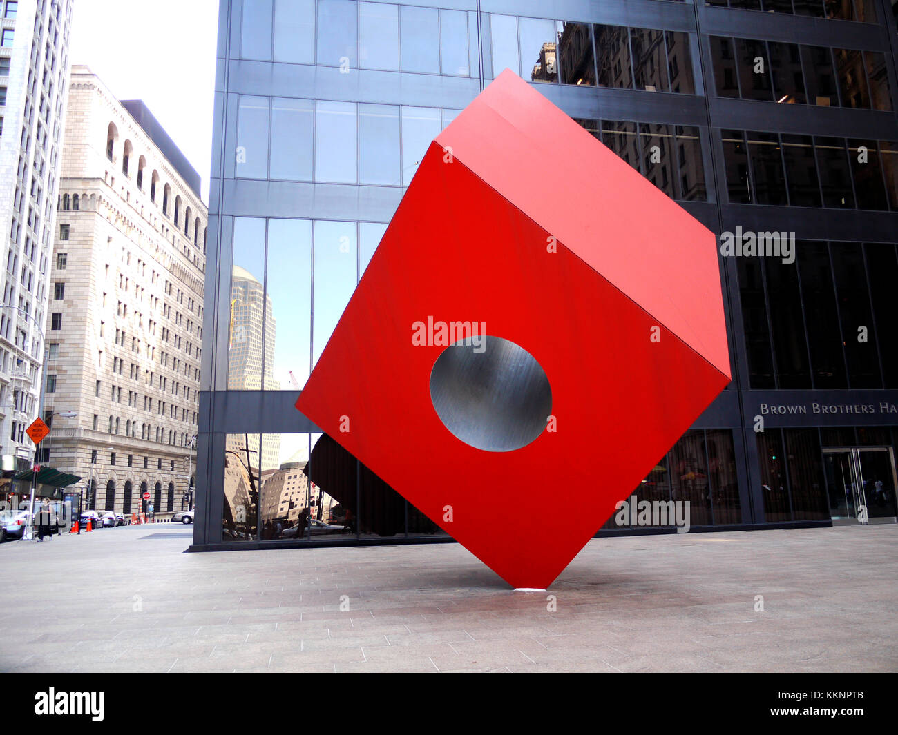 Red Cube, a 1968 sculpture by Isamu Noguchi which sits on Broadway, between Liberty and Cedar streets in New York's - Stock Image