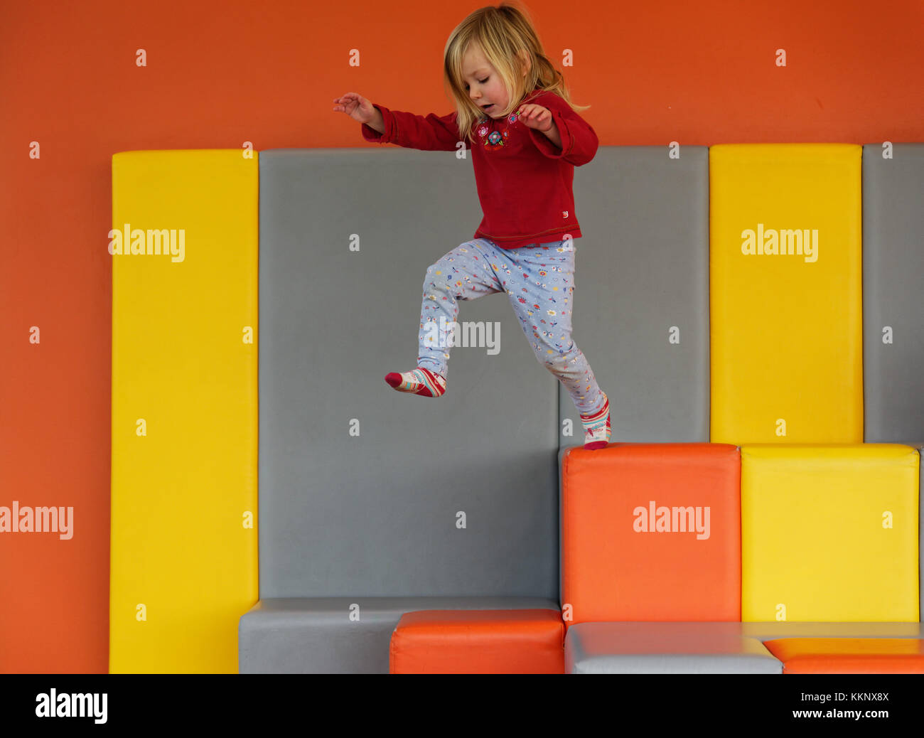 A little girl (3 yrs old) jumping in a padded play area - Stock Image