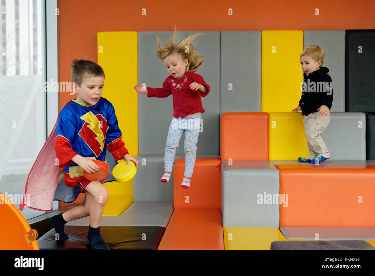 Children playing and jumping in an indoor padded play area - Stock Image