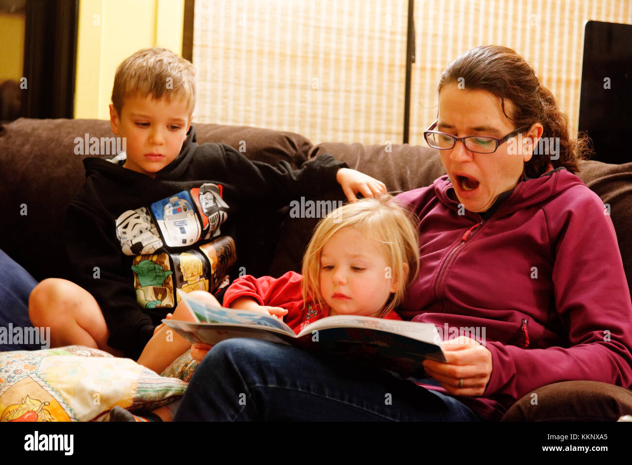 A tired mother yawning while reading out loud to her young children (5 and 3 yrs old) - Stock Image