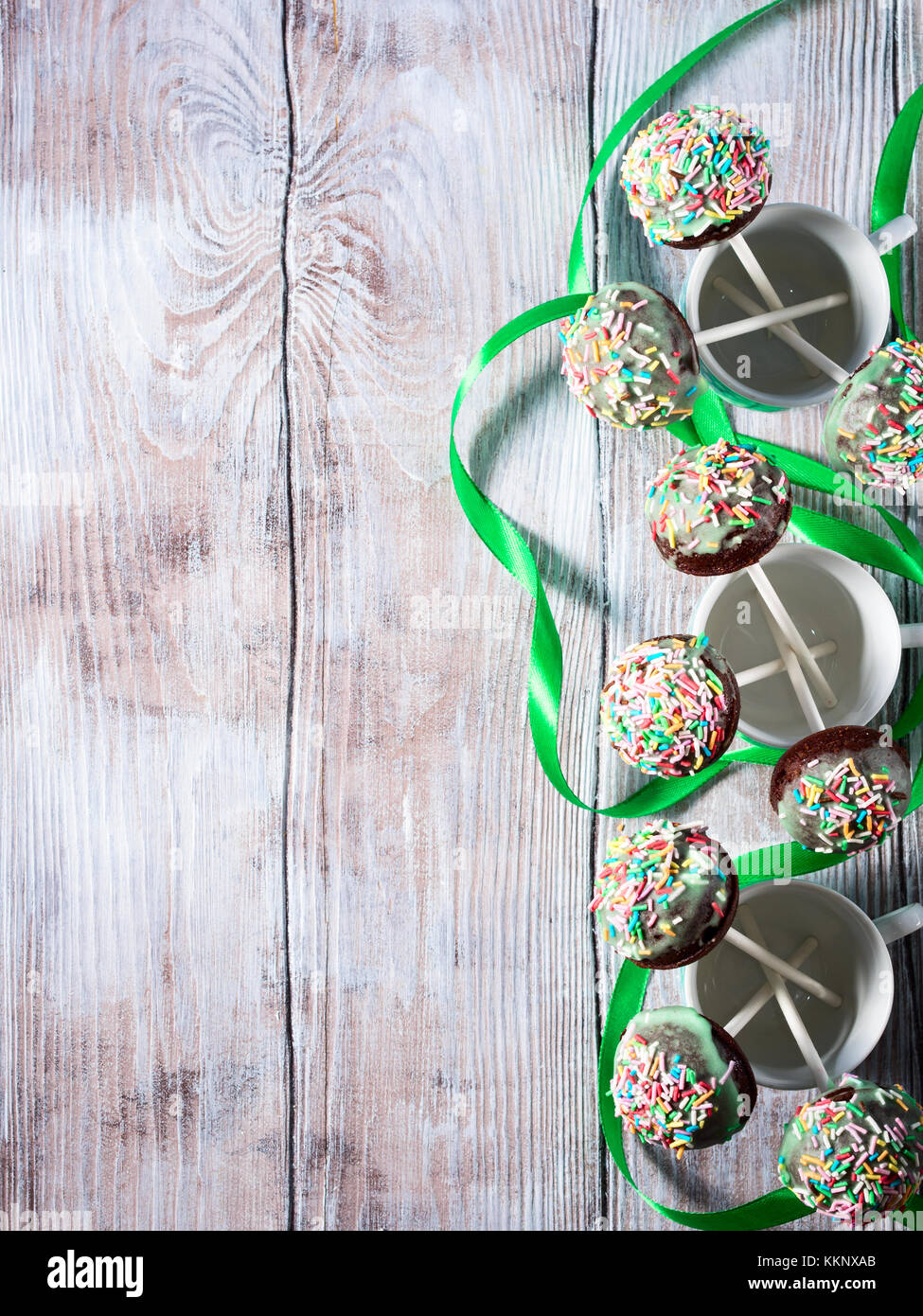 Closeup of colorful chocolate cake pops with sugar sprinkles in small coffee cups on wooden table. Copy space. Top Stock Photo