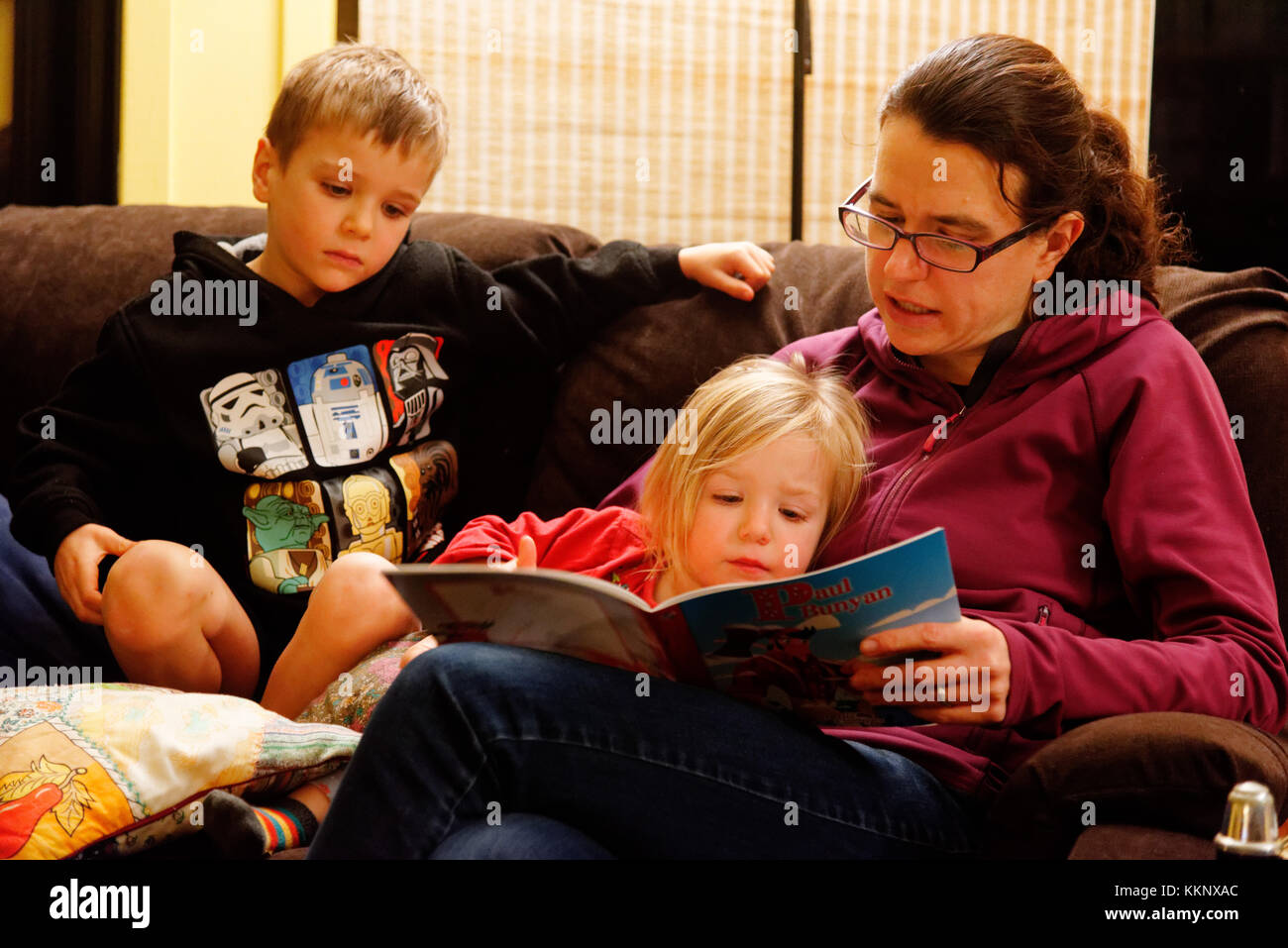 A mother reading out loud to her two young children (5 and 3 yrs old) - Stock Image
