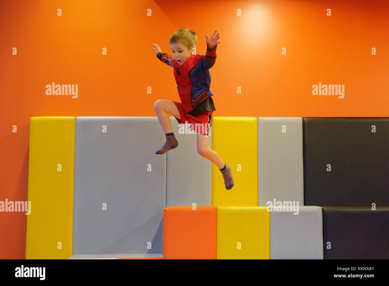 A little boy (5 yrs old) jumping in a padded play area - Stock Image