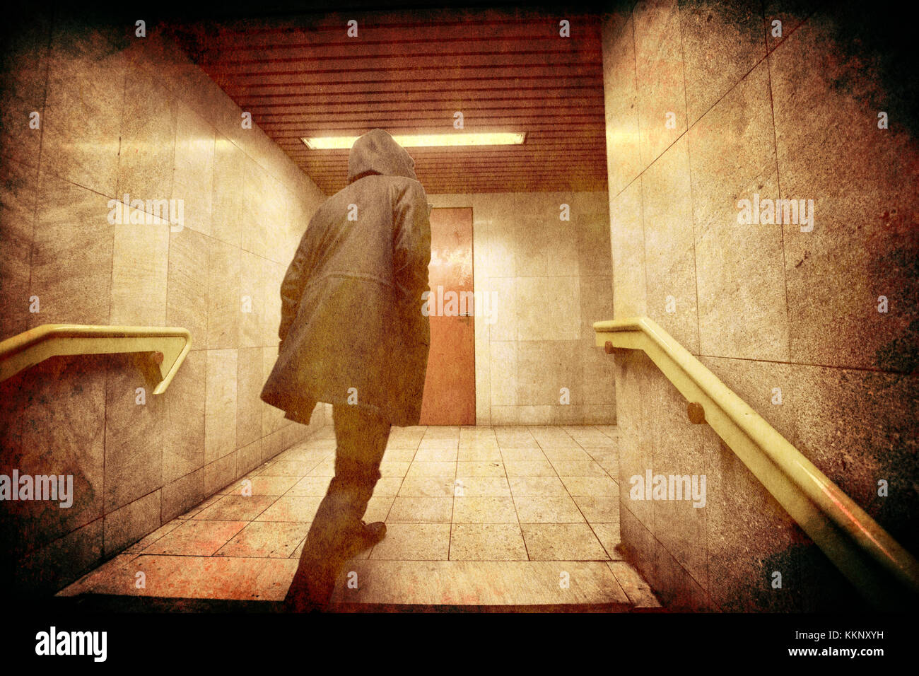 Hooded man comes up from the stairs - Stock Image