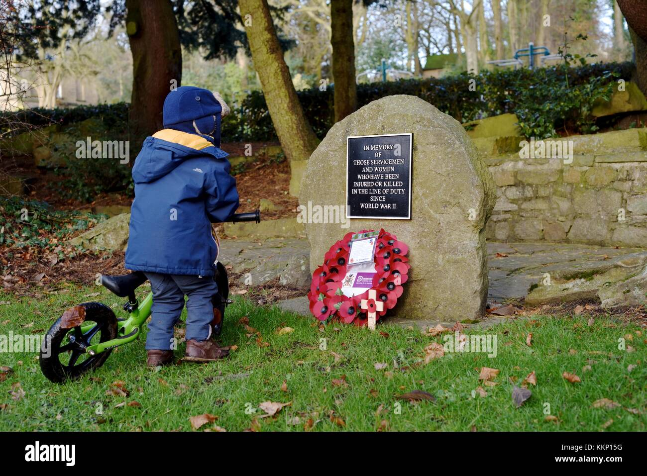 A young boy looks a wreath placed on a war memorial stone in High Lea Park, New Mills, Derbyshire. - Stock Image