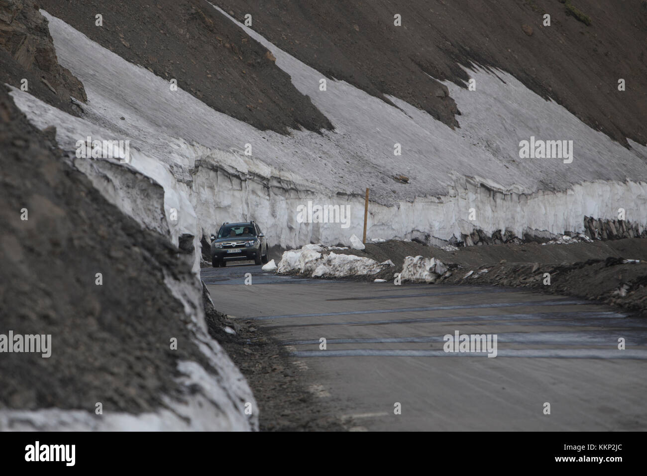 A car drives along mountain road bordered by snow at Col de la Bonette, France in June 2017 Stock Photo