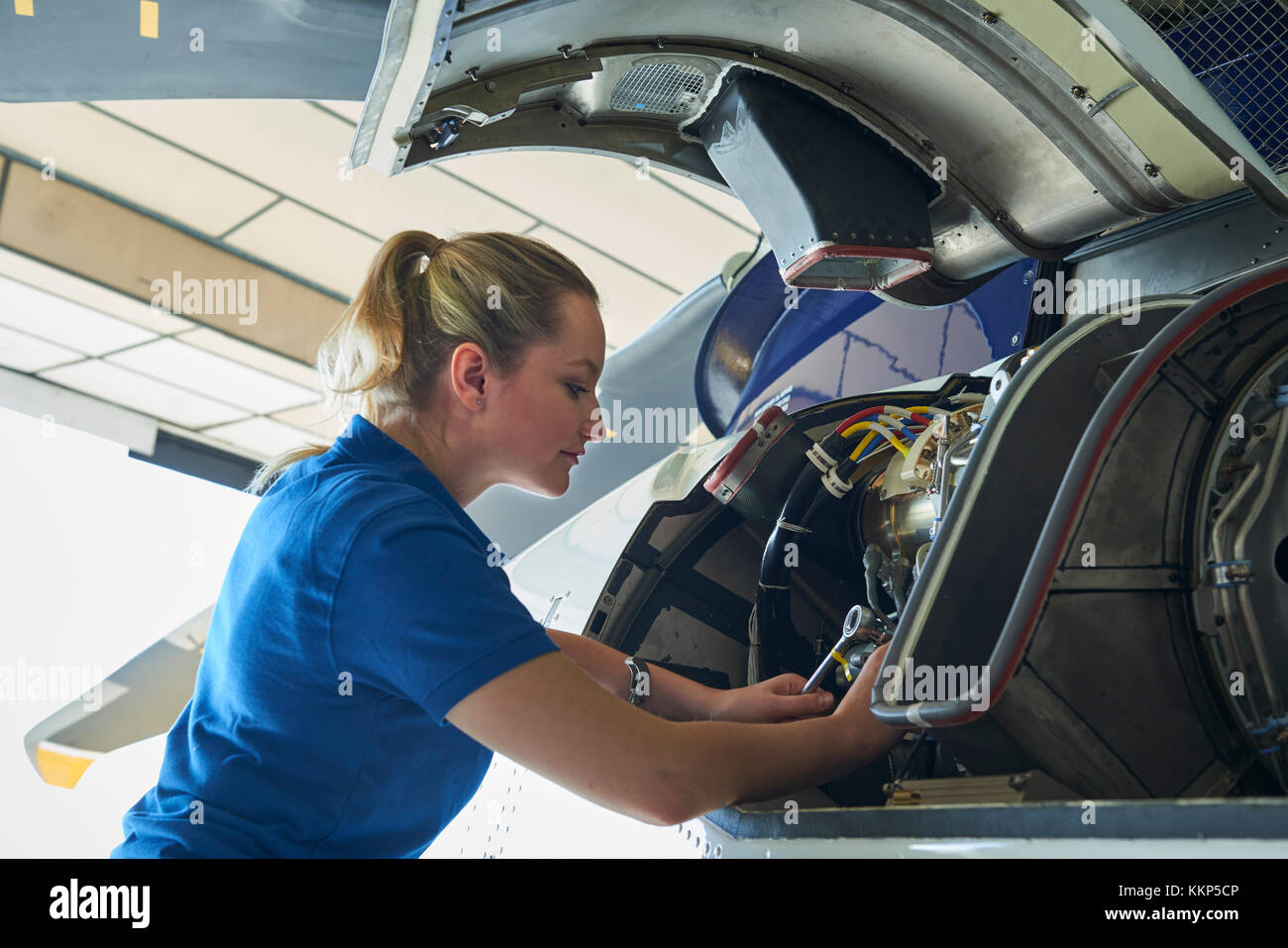 Female Aero Engineer Working On Helicopter In Hangar - Stock Image