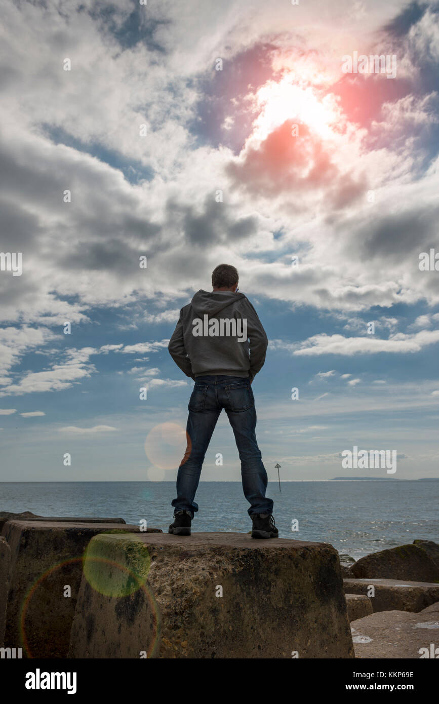 back view of a man standing on sea defence looking out to sea. Lens flare. - Stock Image