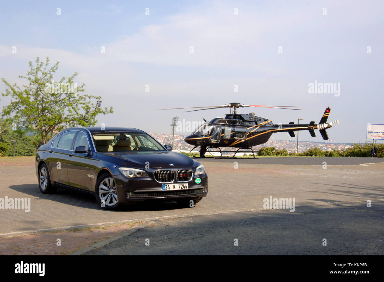 Helicopter waiting to transfer VIP passengers to a BMW 730 LD long wheelbase limo in Istanbul - Stock Image