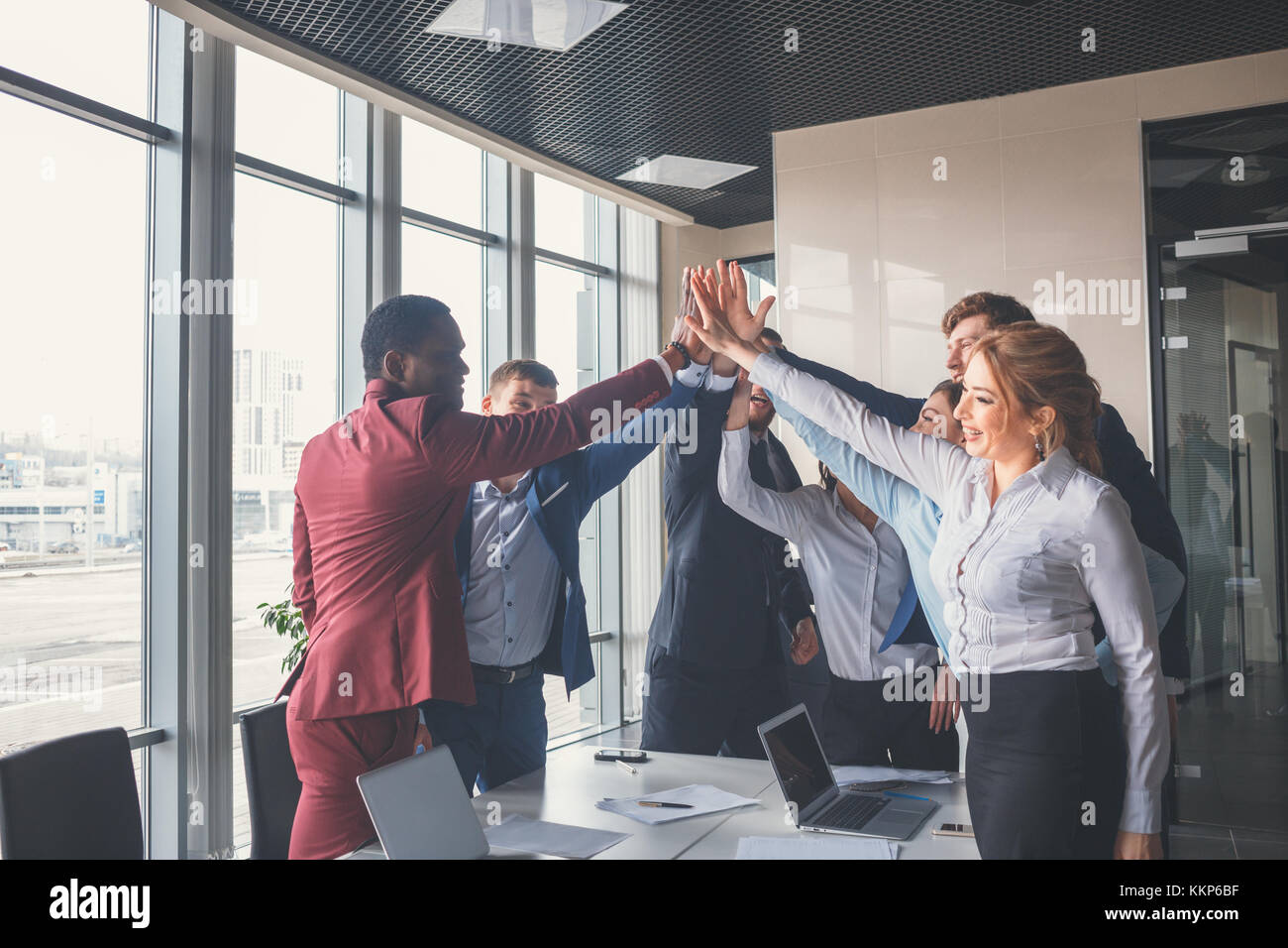 business team giving a high fives gesture as they laugh and cheer their success - Stock Image