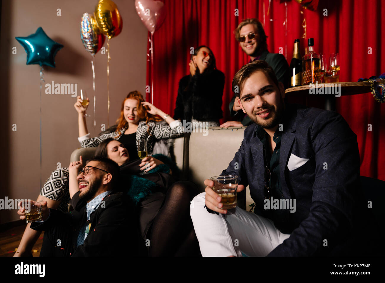 Young man on a party with partying people in background - Stock Image